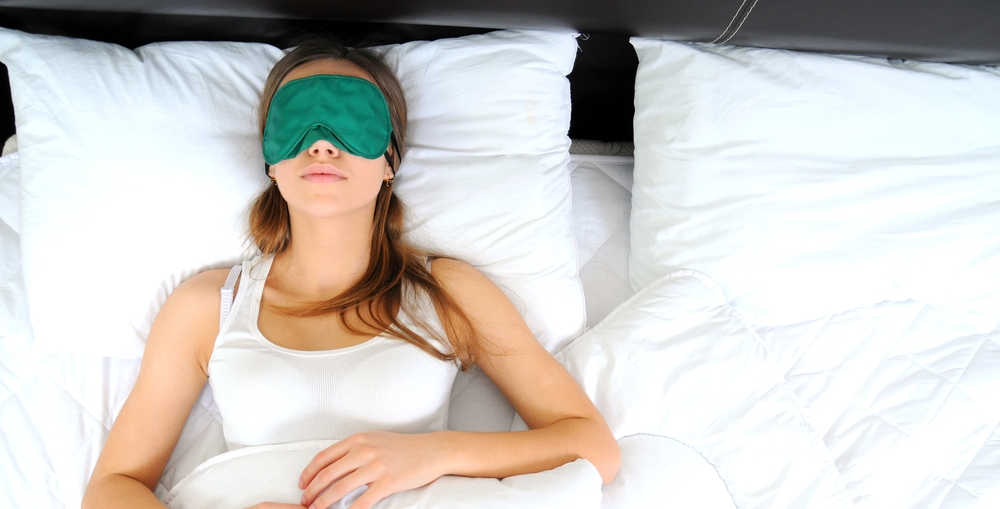 woman wearing sleep mask while lying in bed