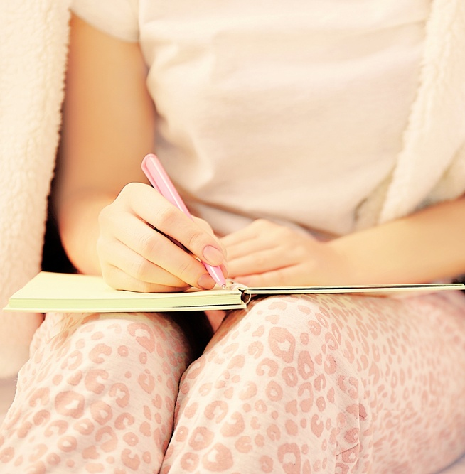woman in pajamas writing in journal